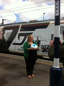 Sharon from Pudsey and West Leeds Clandestine Cake Club having her photo taken with the Skyfall train on York Station.