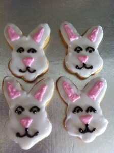 Vanilla shortbread cookie rabbit faces iced with piped royal icing.