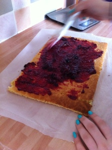 My daughter spreads the jam onto the top of her Swiss Roll.